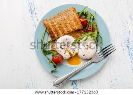 Poached Eggs with Wholegrain Bread Toasts and Vegetables - stock photo
