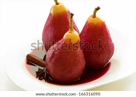 Poached pears in red wine with cinnamon and anise. White plate and white background. - stock photo