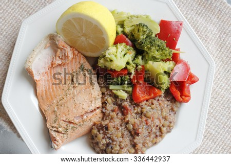 Poached wild salmon with dill herb, tricolor quinoa, lentil and vegetables recipe with green broccoli florets and red sweet bell pepper with a lemon half