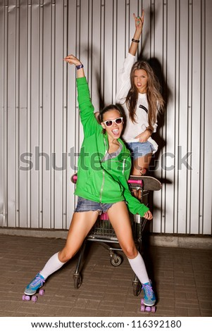 Poartrait of two naughty girls with shopping cart. outdoors - stock photo