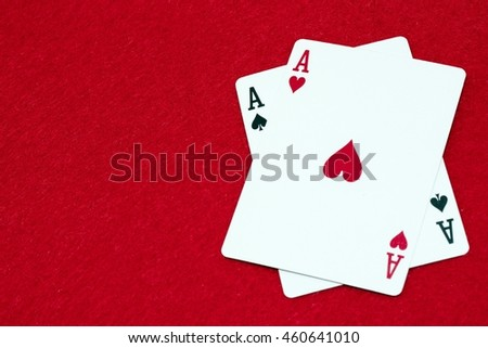 Pocket aces hole cards on red background with copy space - the best startinghand in texas holdem poker
