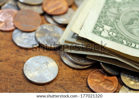 Pocket change dollars and cents on old wood background - stock photo