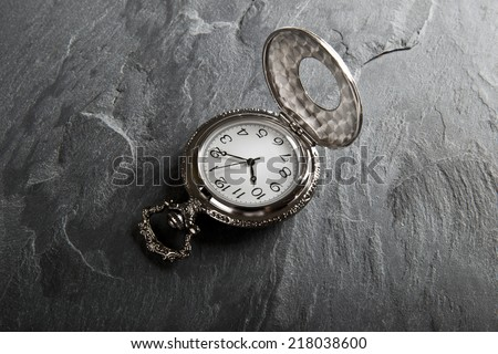Pocket gray clock on dark gray slate texture - stock photo