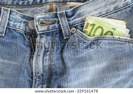 Pocket money in blue jeans - Hundred Euro Note. Selective focus - stock photo