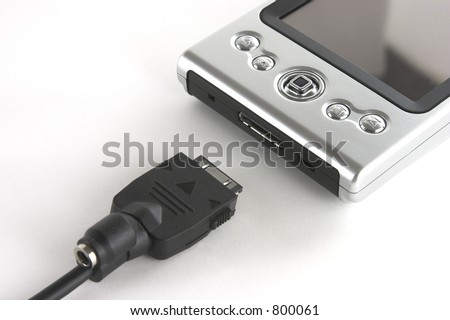 Pocket PC and sync cable isolated over white background