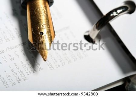 Pocket planner calendar with fountain pen concept - stock photo