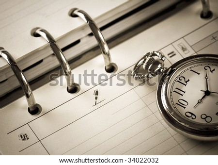pocket watch and agenda - stock photo