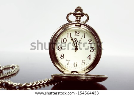 pocket watch and chain on a black background