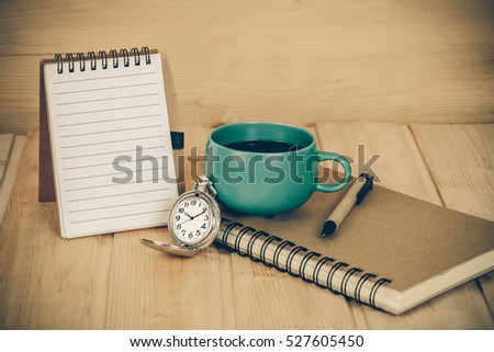 pocket watch and coffee cup on book with vintage tone
