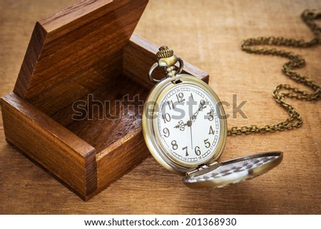 Pocket watch and wooden box - stock photo
