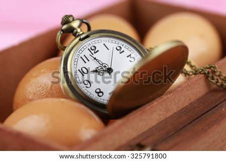 pocket watch in an old wood box with egg and egg tart - stock photo
