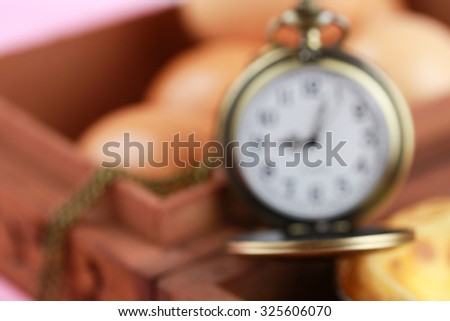 pocket watch in an old wood box with egg as blurred  - stock photo