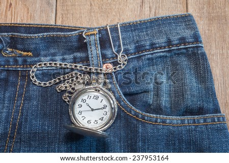 pocket watch in pocket of jeans - stock photo