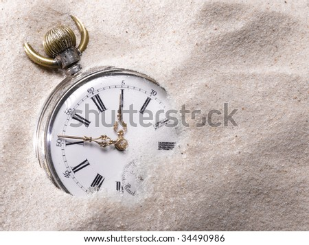 Pocket watch in sand - stock photo