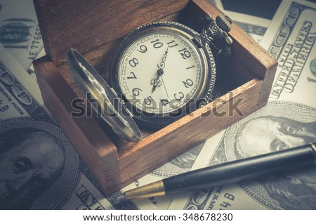 Pocket watch in wood box with pen and money. - stock photo