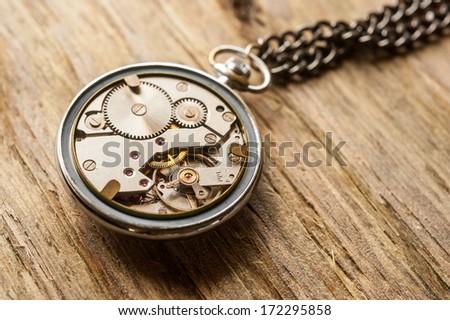 pocket watch mechanism on wood background - stock photo
