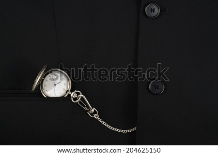 Pocket watch on a chain in a pocket of a black business suit as a backdrop composition - stock photo