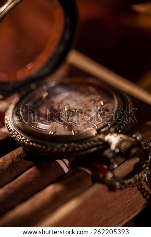 Pocket watch on a chain lying on top of the package of Cuban cigars