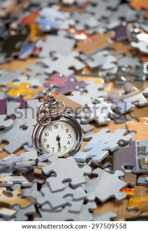 Pocket watch on a pile of jigsaw puzzle pieces. Shallow depth of field - stock photo