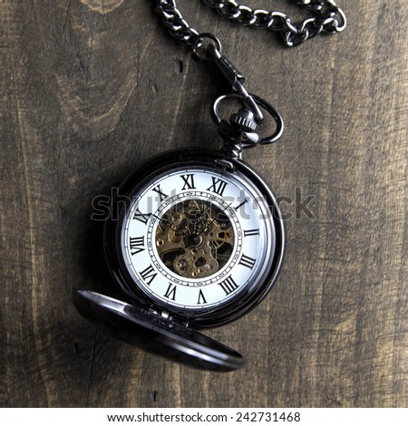 pocket watch on grunge wooden table, from above - stock photo