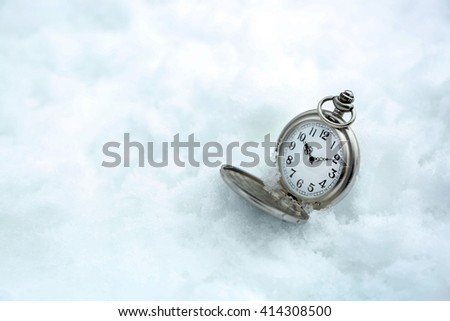 Pocket watch over white snow background - stock photo
