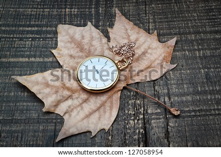 Pocket watch the autumn leaves. On a wooden texture. - stock photo