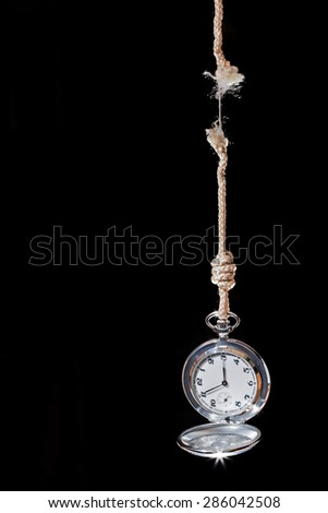 pocket watch time is ending on a black background - stock photo