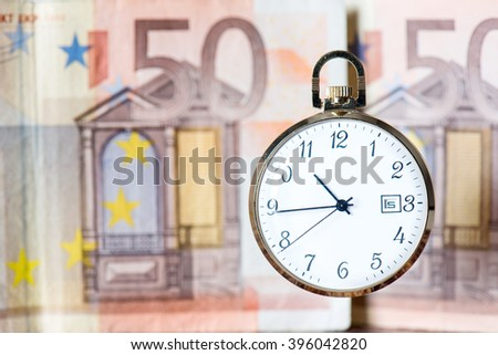 pocket watch with euro banknotes and coins, still life - stock photo