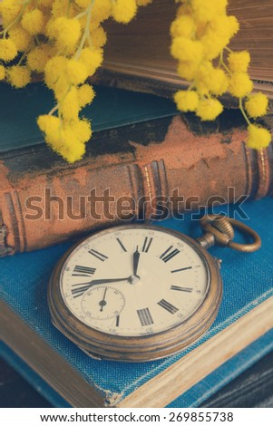 pocket watch with stack of vintage old books, retro toned  - stock photo