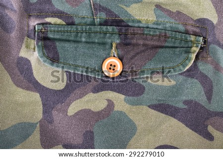 Pocket with a button on the fabric with a camouflage pattern. Background. - stock photo