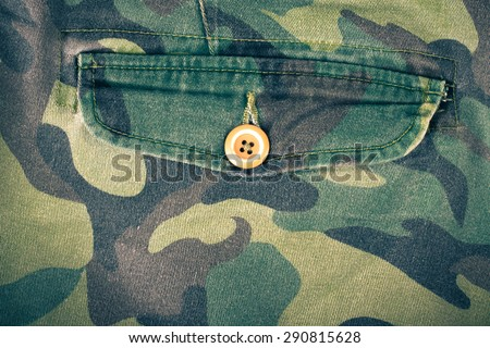 Pocket with a button on the fabric with a camouflage pattern. Background. Toned. - stock photo