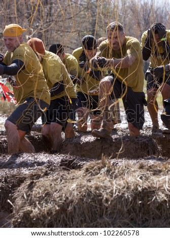 POCONO MANOR, PA - APR 29: A team runs through an obstacle with electrified wires at Tough Mudder on April 29, 2012 in Pocono Manor, Pennsylvania. The course is designed by British Royal troops. - stock photo