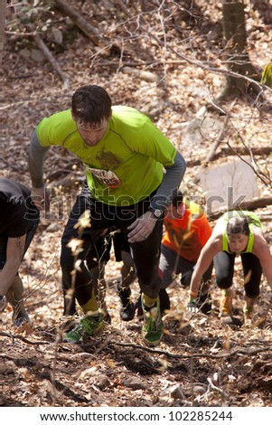 POCONO MANOR, PA - APR 28: Participants run up a steep hill through the woods at Tough Mudder on April 28, 2012 in Pocono Manor, Pennsylvania. The course is designed by British Royal troops. - stock photo