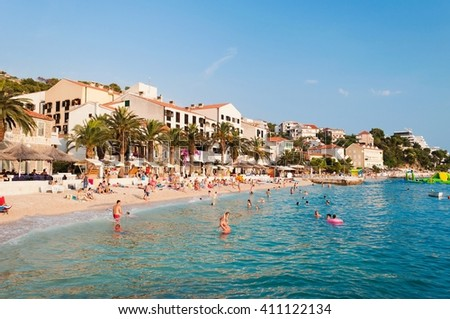 PODGORA, CROATIA - JULY 20, 2013: People swim and sunbathe at the amazing beach of Podgora with hotel Podgorka in background. Podgora is a popular holiday resort in Croatia. - stock photo