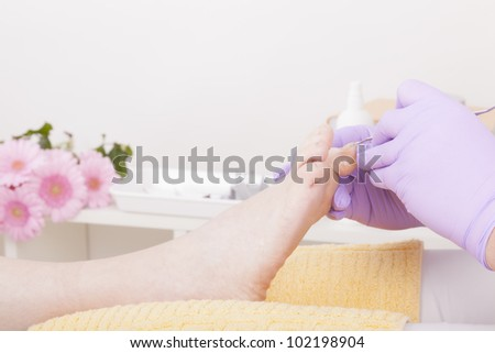 podiatrist ( chiropodist ) at work,cleaning womans feet.