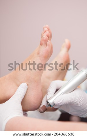 podiatrist ( chiropodist ) cleaning womans feet ( toenails ) - stock photo