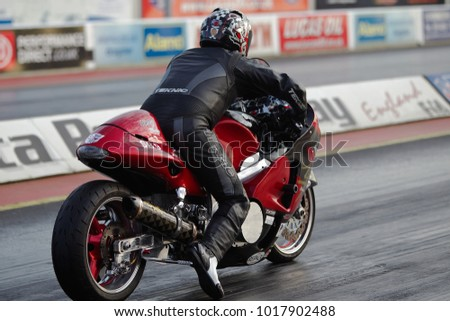 PODINGTON, UK - APRIL 11: A modified road based motorcycle is stood at the start line on Santa Pod Raceway before heading down the drag strip at the Big Bang festival on April 11, 2014 in Podington