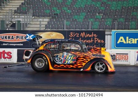 PODINGTON, UK - April 11: Colin Millar prepares his drag car for a run by warming the tyres with a controlled burnout at the Big Bang event held at Santa Pod on April 11, 2014 in Podington