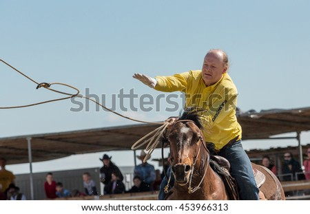 Podmitrov, CZE - MAY 7, 2016:Man in yellow shirt is throwing a lasso a bull races in Mitrov, Czech republic