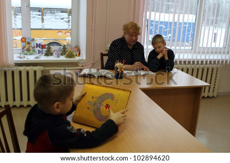 PODPOROZHYE, RUSSIA - JANUARY 31: Open Day at the Podporozhye's Children House - unknown children in the library read books with teachers, January 31, 2010 in Podporozhye, Russia. - stock photo