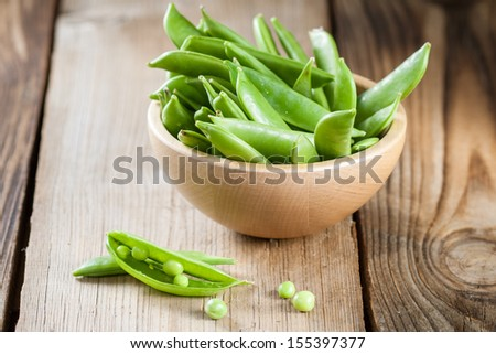 Pods of green peas in a wooden bowl