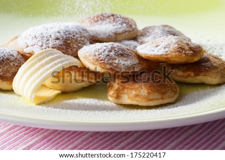 poffertjes with powdered soft sugar on a dinner plate