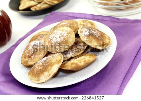Poffertjes with sweet powdered sugar on a light background