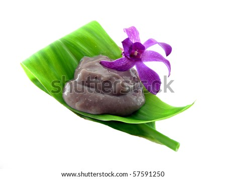 Poi on a tea leaf with an orchid isolated on white.  A popular food in Hawaii made with taro, typically eaten by scooping with two fingers.