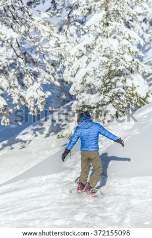 POIANA BRASOV, ROMANIA - JANUARY 24, 2016: Snowboarder sliding on ski slope during winter season in Poiana Brasov resort, Romania - stock photo