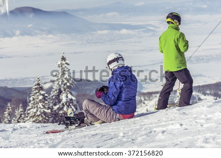 POIANA BRASOV, ROMANIA - JANUARY 24, 2016: Snowboarders sitting on the sky slope in Poiana Brasov, Romania - stock photo