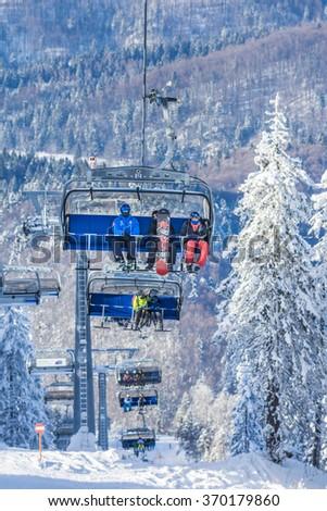 POIANA BRASOV, ROMANIA - JANUARY 24, 2016:Tourists in chairlift in winter season going to the ski slope in resort Poiana Brasov, Romania - stock photo