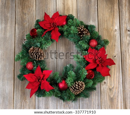 Poinsettia flower Christmas wreath on rustic cedar wood.