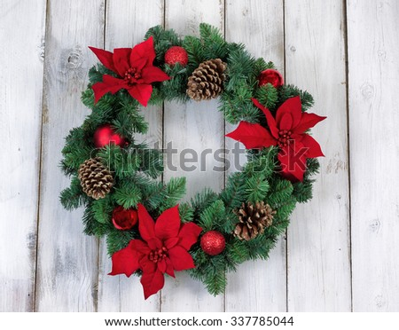 Poinsettia flower Christmas wreath on rustic white wood.