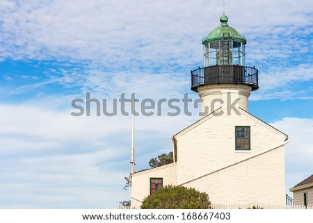 Point Loma lighthouse profile. Side view of white building. Fresnel lens visible in tower. Cloudy blue sky background. Room for text, copyspace. Horizontal photo.